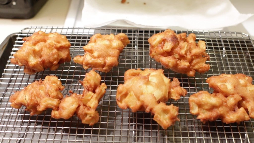 Freshly fried apple fritters on a wire rack lined sheet pan.