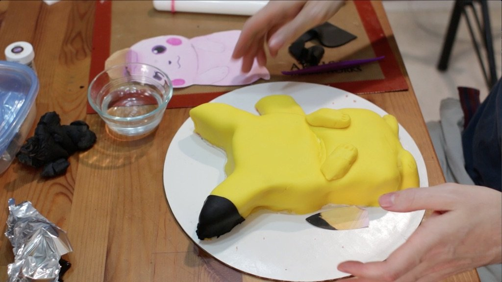 Black fondant wrapped around one of the pikachu's ears.