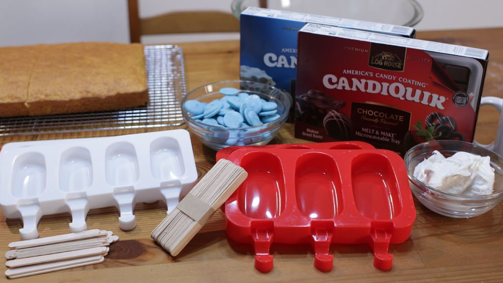 Cakesicle molds, popsicle sticks, frosting, candy melts, chocolate and cake on a wooden table.