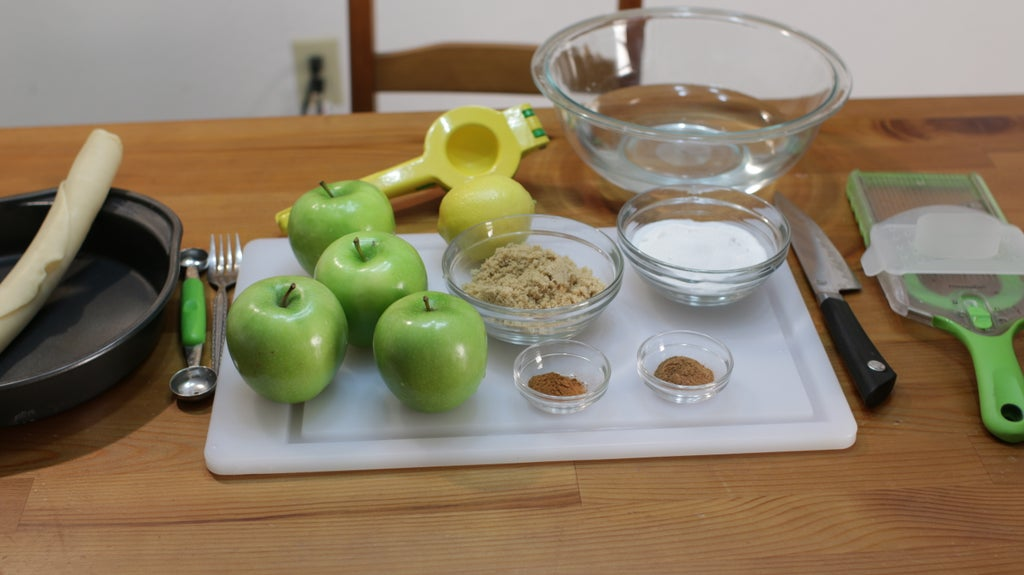 Several ingredients in bowls, sugar, spices, etc. Apples on the table.