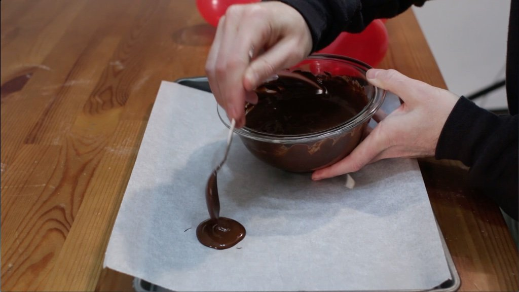 Hand pouring a round circle of chocolate on a sheet pan lined with parchment paper.