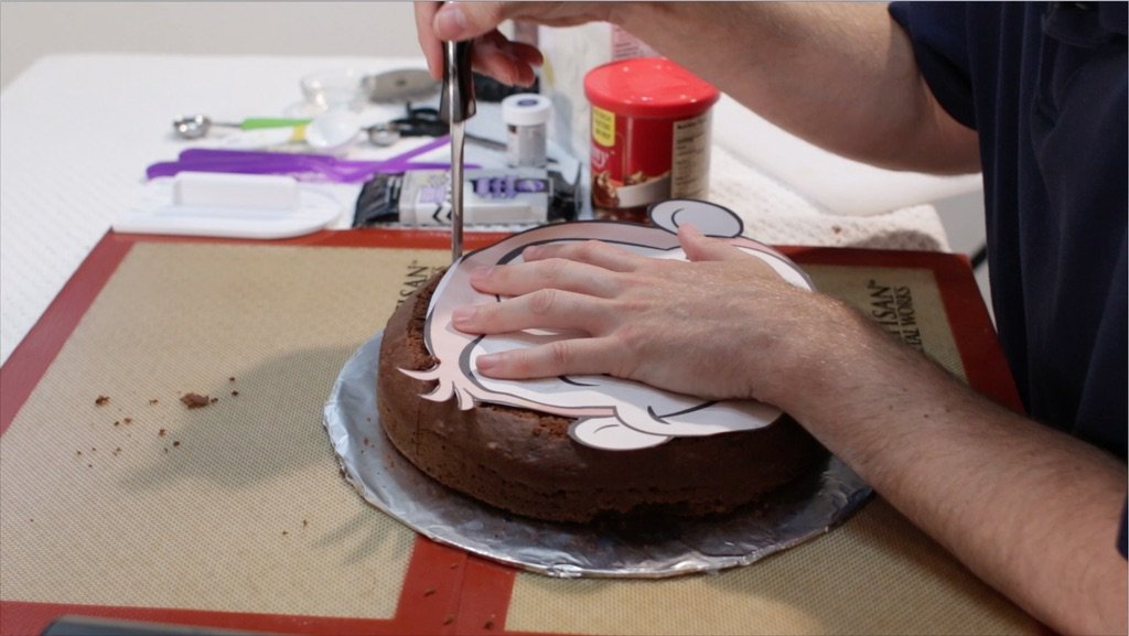 Hand cutting around a curious george stencil on a chocolate cake