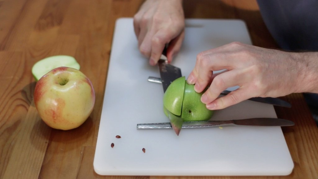Hand cutting an apple wedge out of a piece of apple.