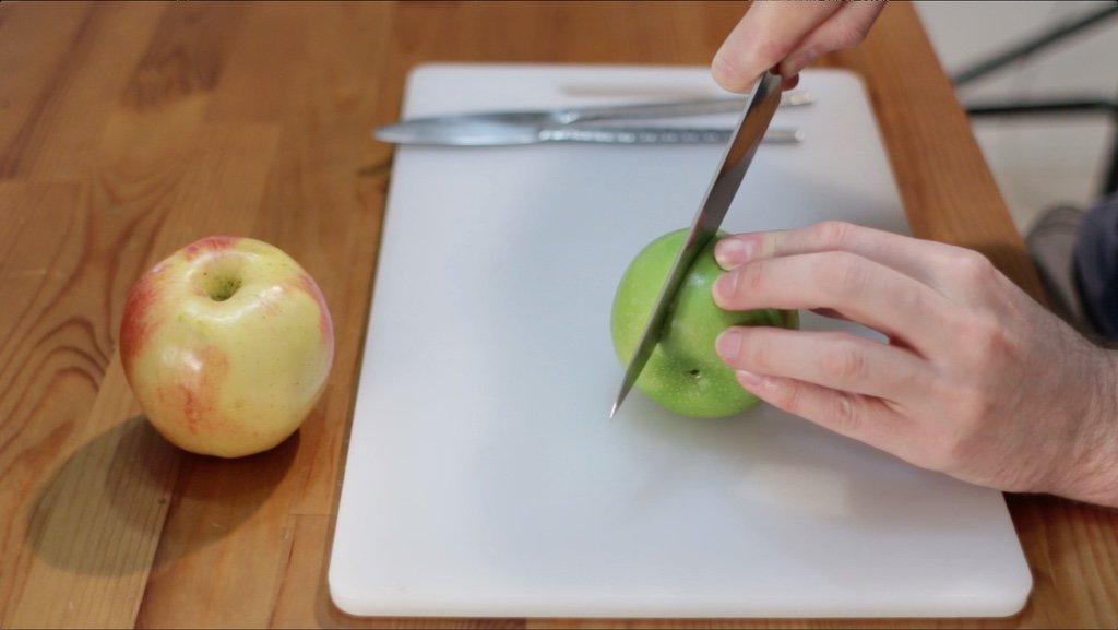 Hand cutting a green apple.