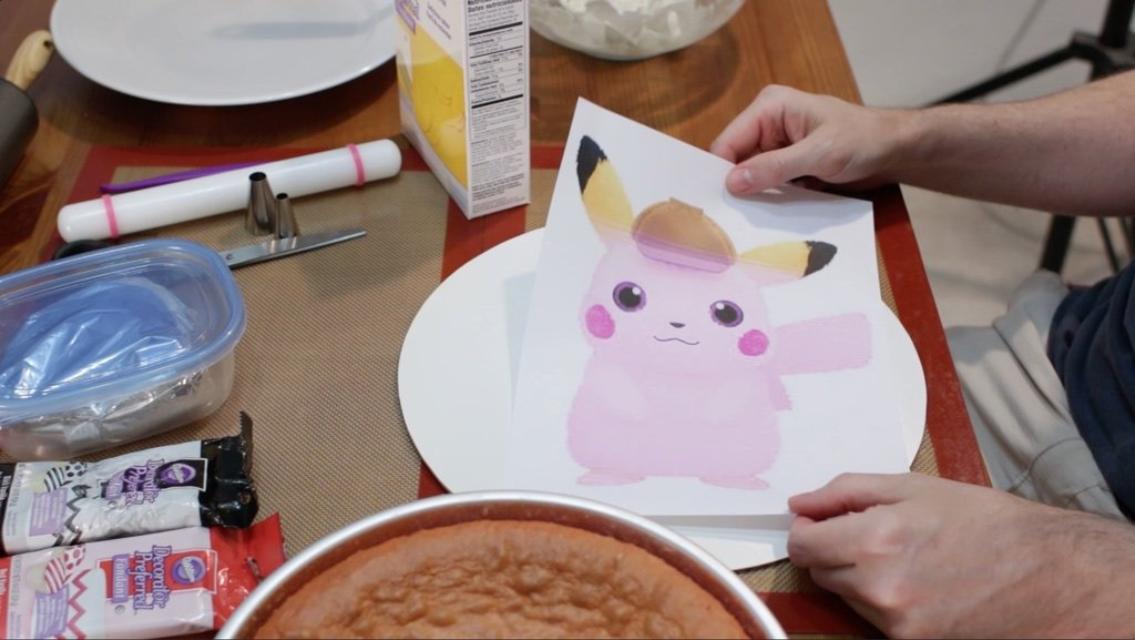 Pokemon Detective Pikachu paper template next to a baked strawberry cake.