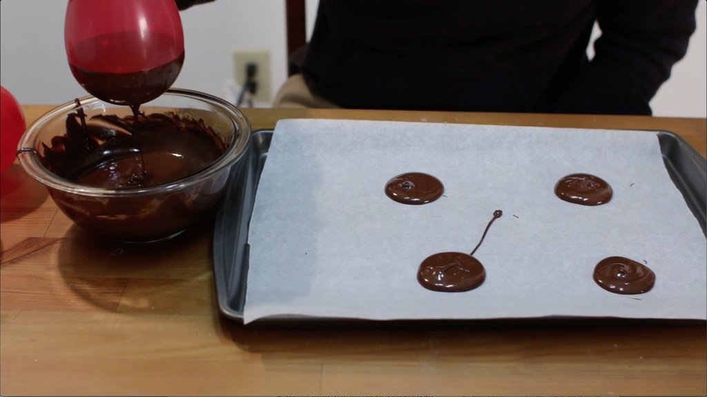 Hand dipping red balloon into chocolate