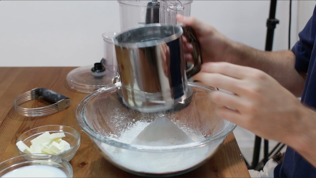 Hand holding metal sifter sifting dry biscuit ingredients into a large glass bowl.
