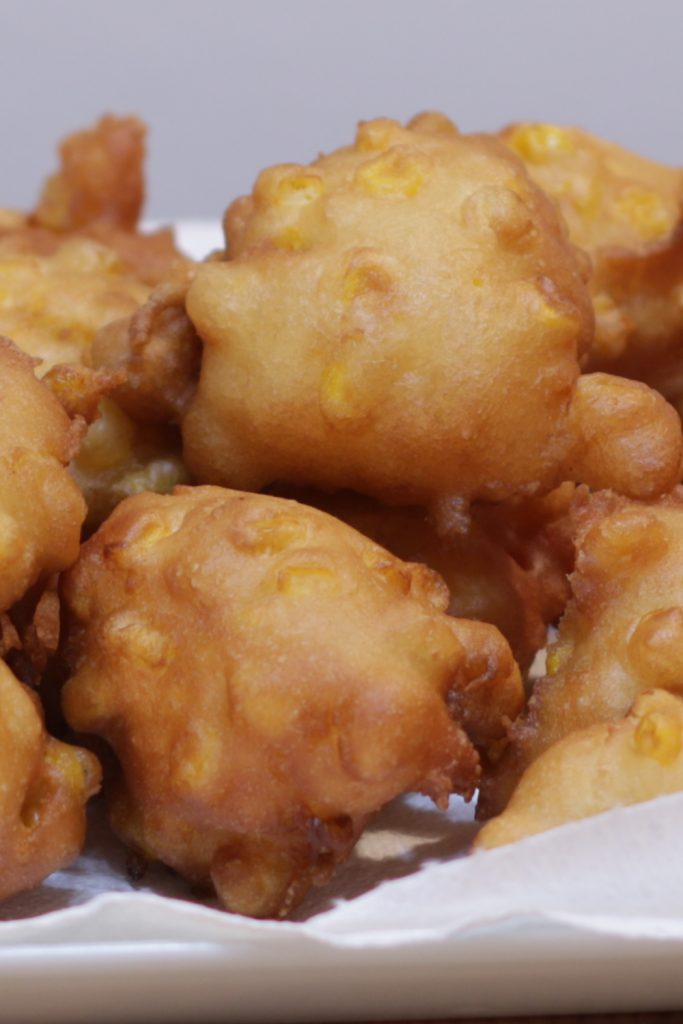 Pile of corn fritters on a white plate.