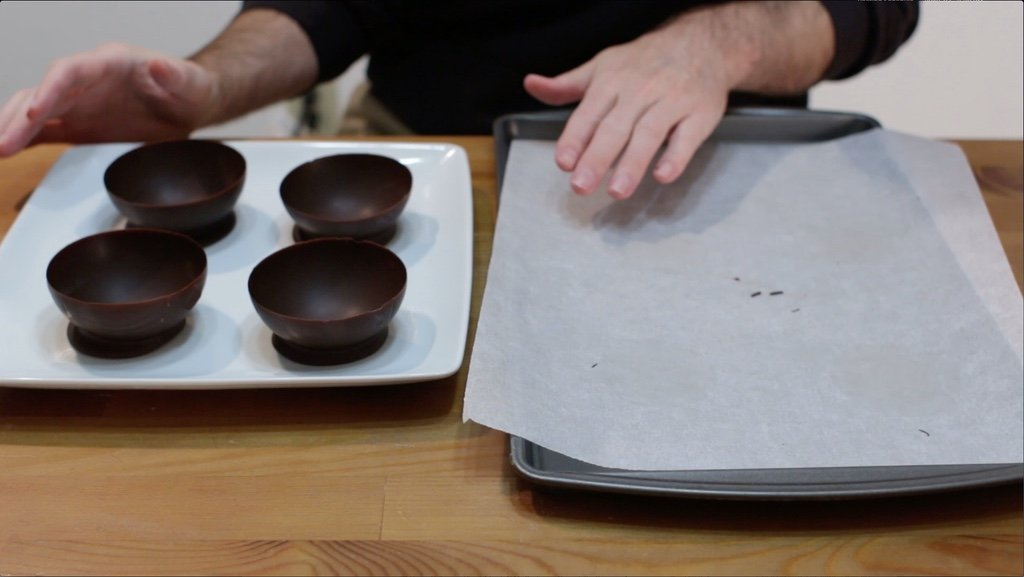 Four empt chocolate balloon bowls on a white plate.