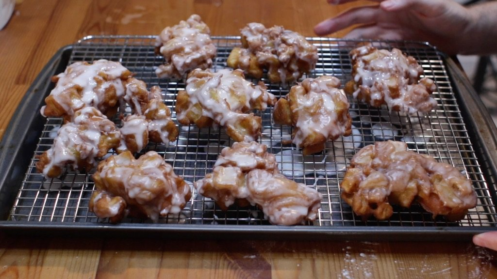 Sheet pan lined with a wire rack full of apple fritters.