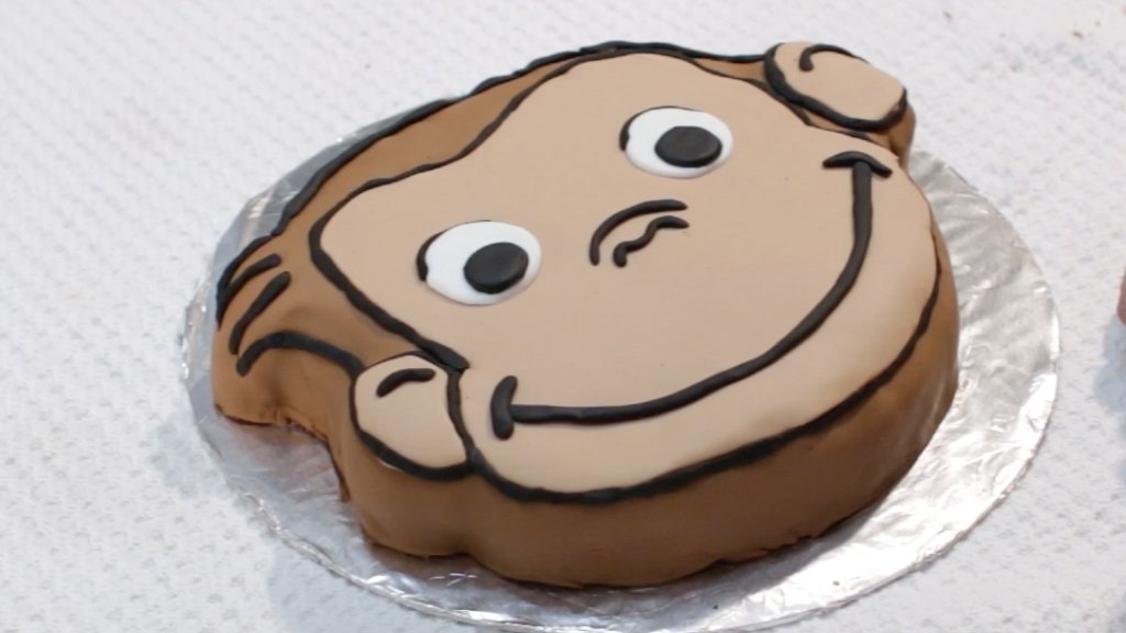 Finished Curious George cake on a cake board on a white table.