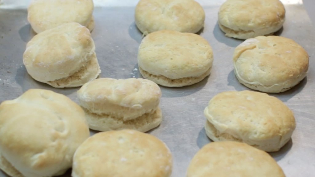 Freshly baked homemade biscuits on a metal sheet pan.
