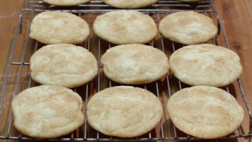 Freshly baked homemade snickerdoodle cookies sitting on a cookie rack.