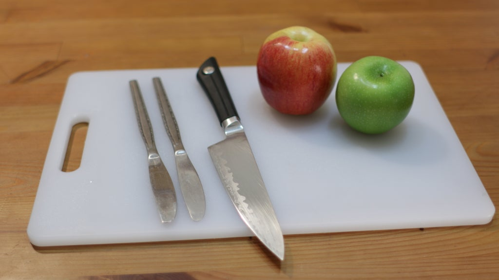Apples and knives on top of a white cutting board.