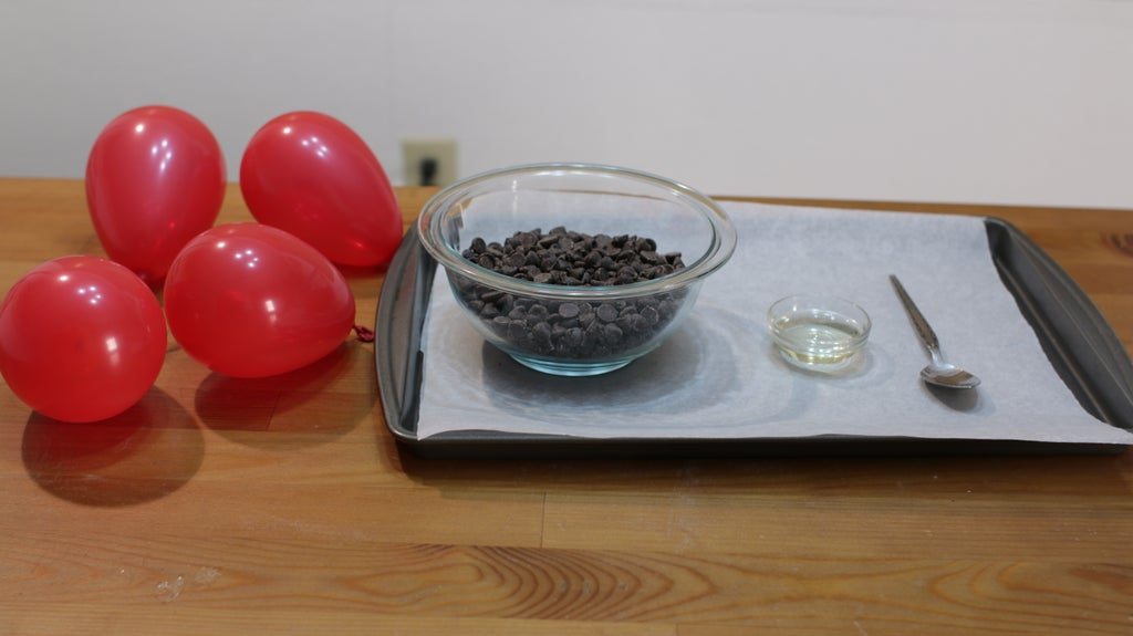 Red balloons and a bowl of chocolate chips and a small glass bowl of oil on a table.