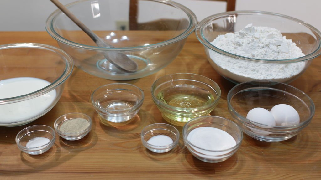 Several ingredients in glass bowls on a wooden table.