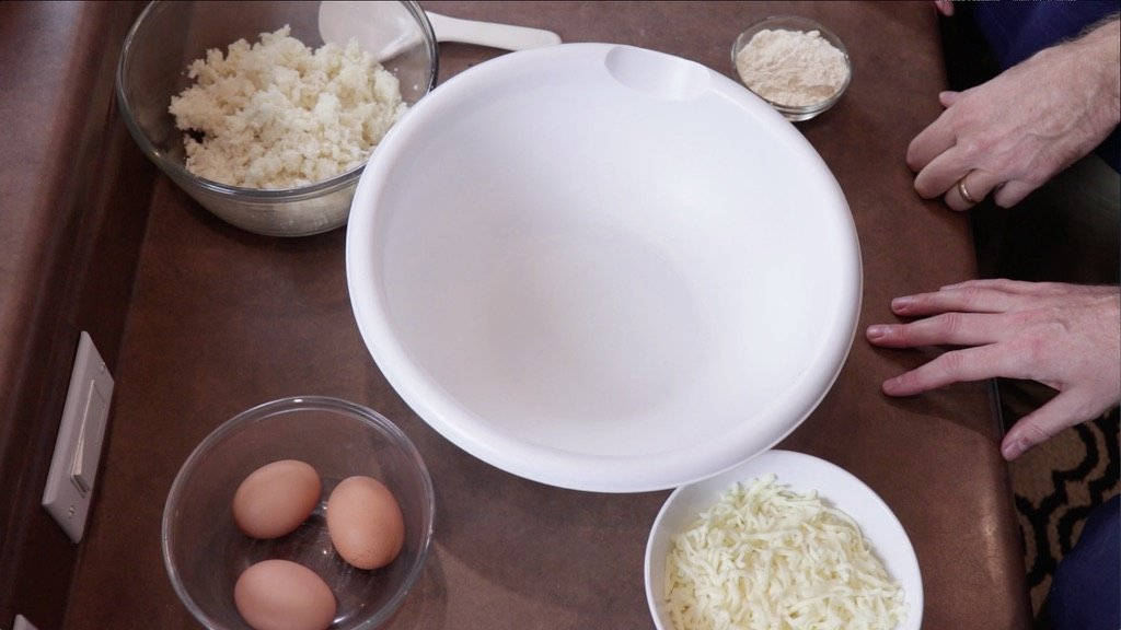 cauliflower, almond flour, cheese and eggs in bowls on a counter.