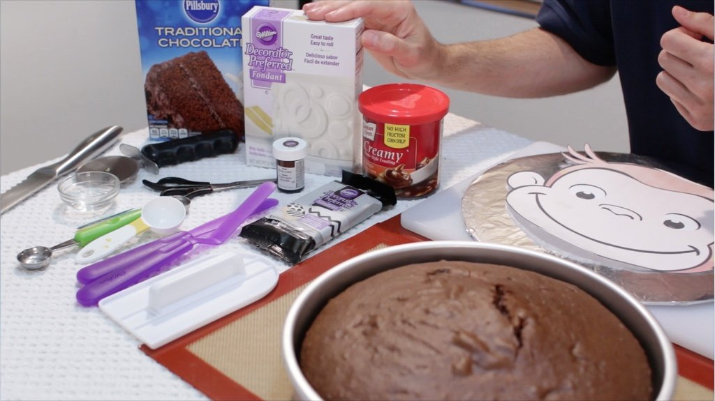 Several ingredients on a table included a baked chocolate cake and a curious george stencil, fondant, frosting, etc.