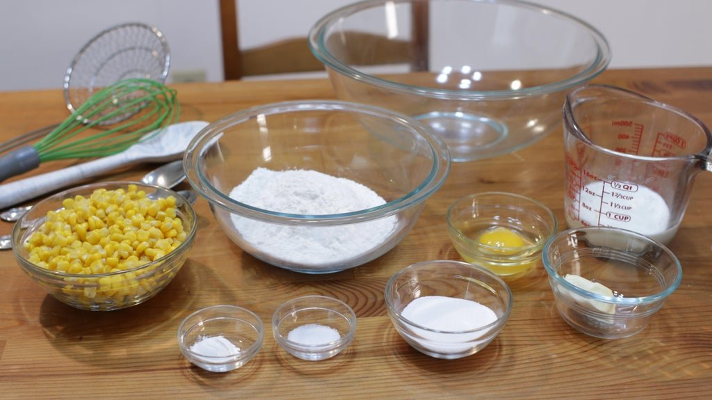 Several ingredients in glass bowls on top of a wooden table, including corn, sugar, flour, milk ,etc.