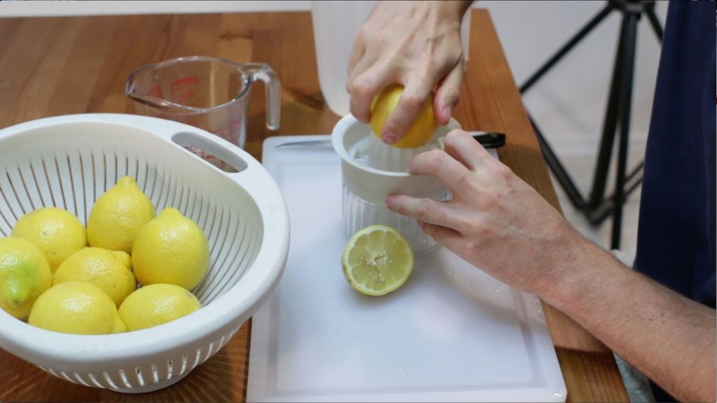 Hand juicing lemons with a white juicer.