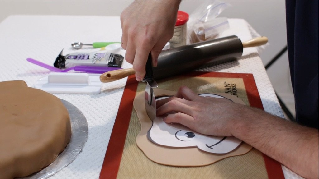 Hand cutting fondant around a curious George face template.