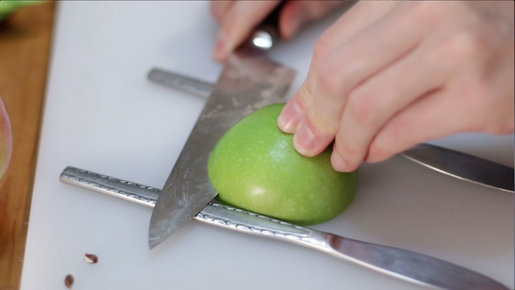 Hand cutting a thin slice of apple with a knife.