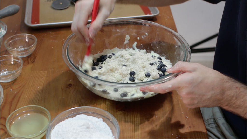 Hand mixing blueberry scones dough in a large glass bowl.