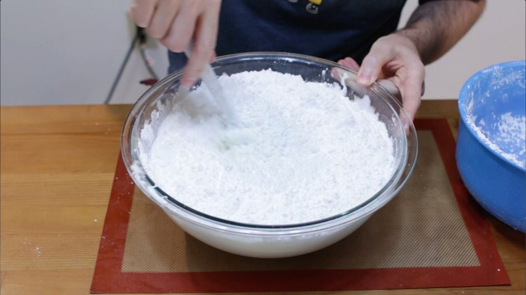 Powdered sugar poured into the large bowl of melted marshmallows.