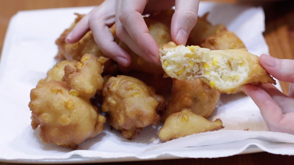 Hand pulling apart a corn fritter.