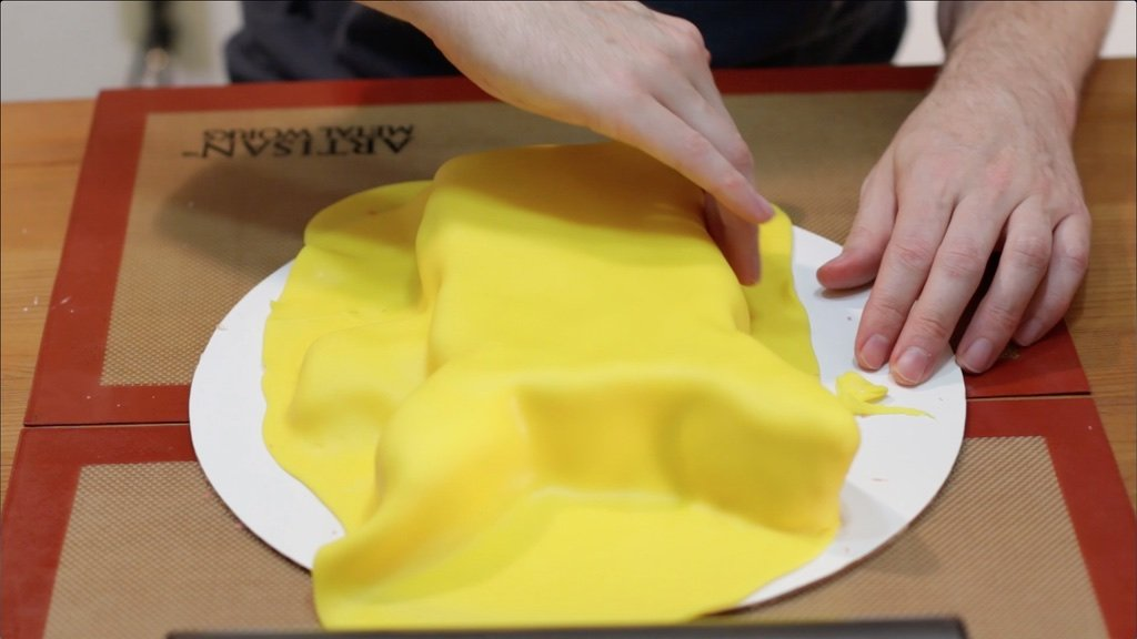 Yellow fondant covering a cake.
