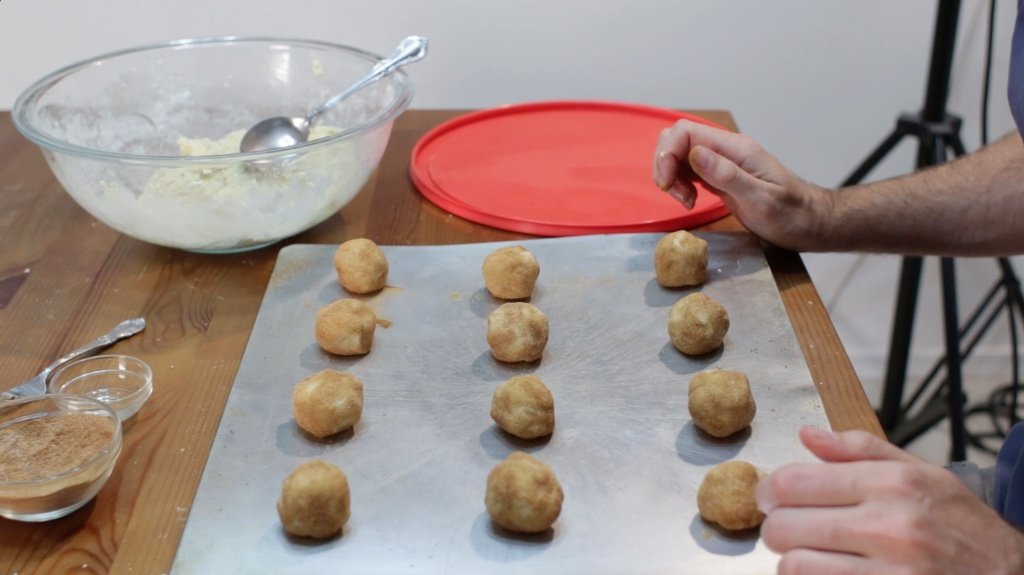 Cookie sheet full of rolled snickerdoodles dough balls.