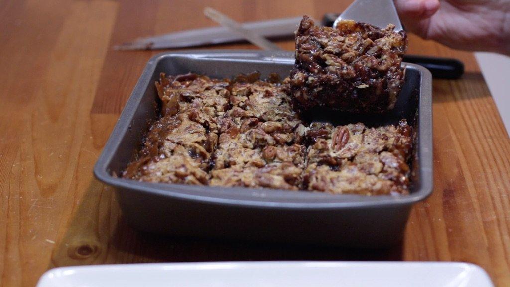 Slice of pecan pie brownie being held by a hand.