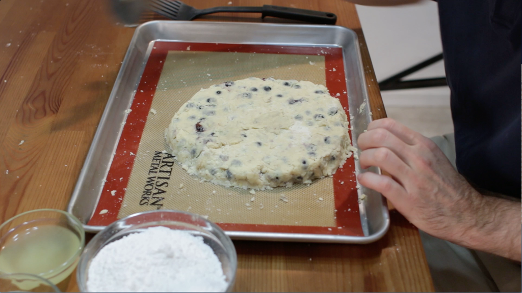 Blueberry scones dough shaped in a circle on a sheet pan lined with a silicone mat.