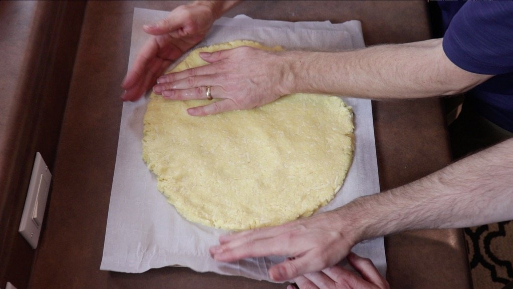 Hand shaping keto pizza crust on a cookie sheet lined with parchment paper.