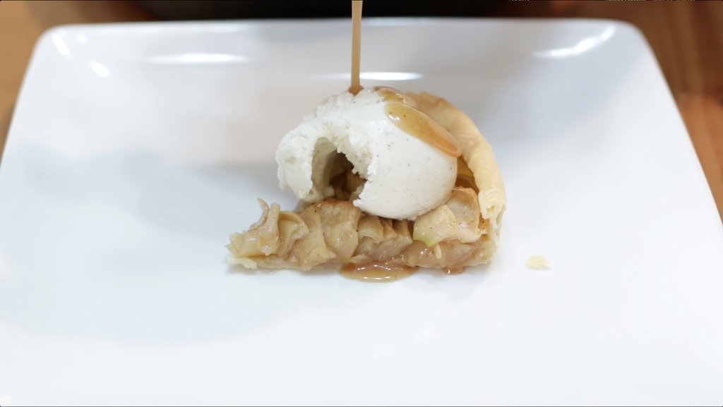 Slice of caramel rose apple pie with a scoop of vanilla ice cream on a white plate.