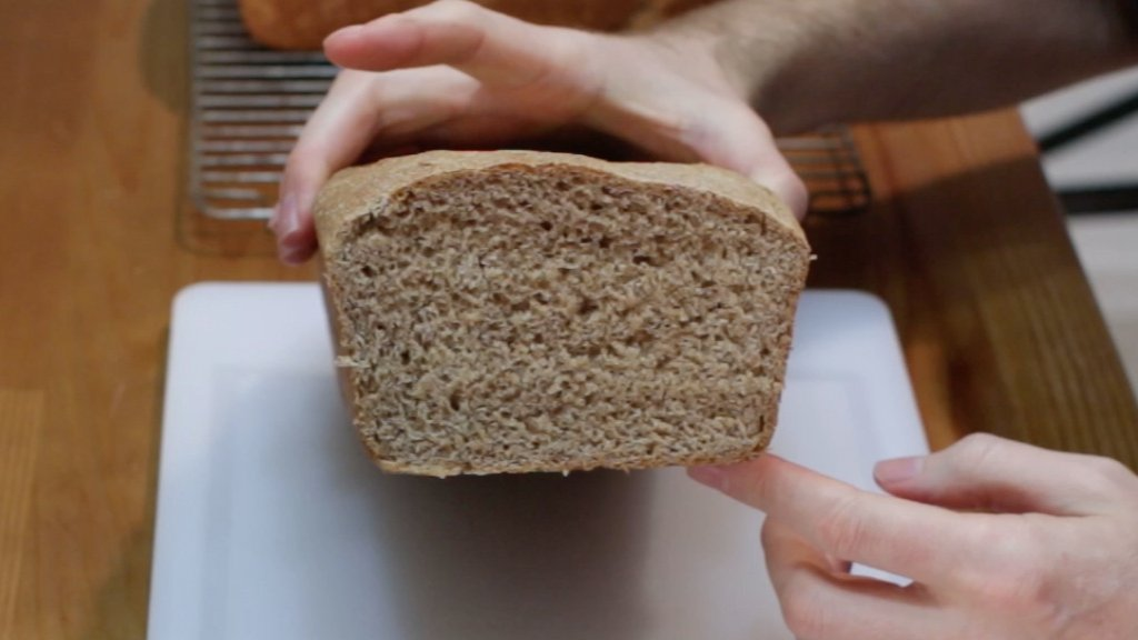 Hand holding a sliced loaf of whole wheat bread.