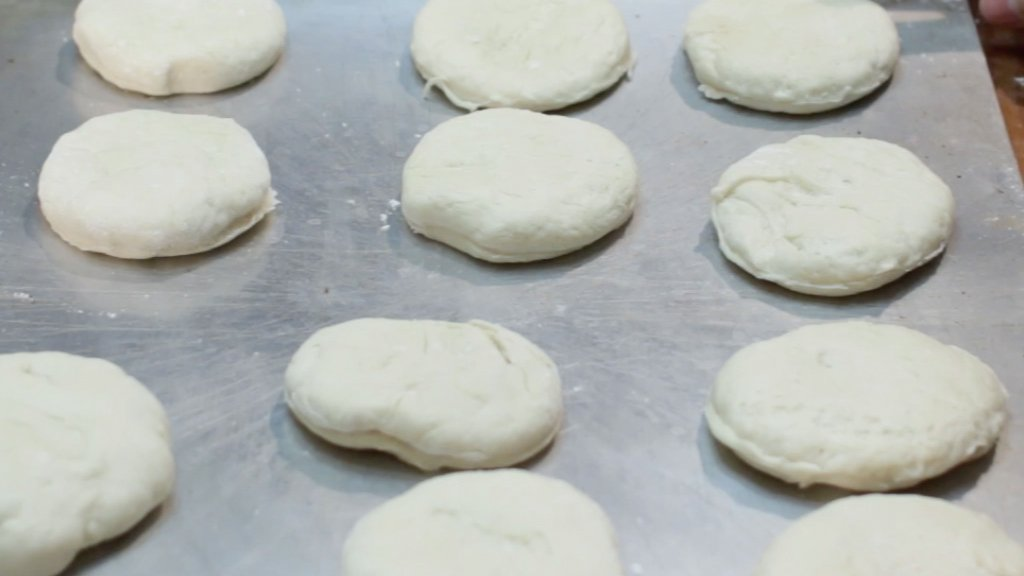 Round unbaked biscuits on a metal cookie sheet.