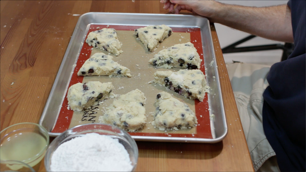 Cut unbaked blueberry scones on a sheet pan lined with a silicone baking mat.
