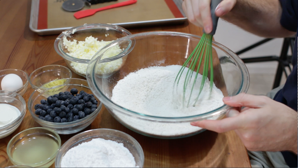 Hand whisking flour and other ingredients in a large glass bowl.