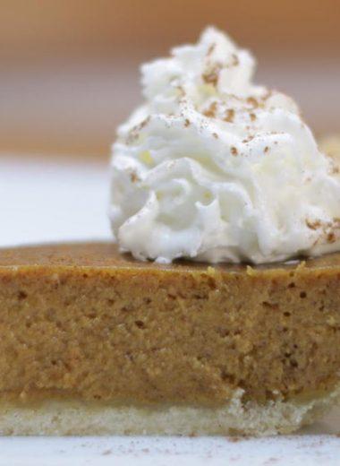Slice of homemade pumpkin pie on a white plate.