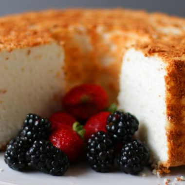 Angel Food cake with strawberries and blackberries on a cake pedestal.