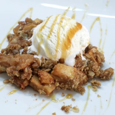 Apple crisp drizzled with caramel on a white plate