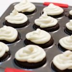 Pan full of homemade chocolate cupcakes with cream cheese frosting