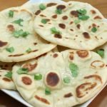 stack of homemade naan on a white square plate on a wooden table.