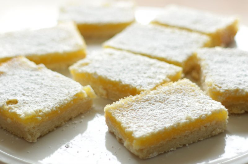 Lemon bars on a white cake pedestal