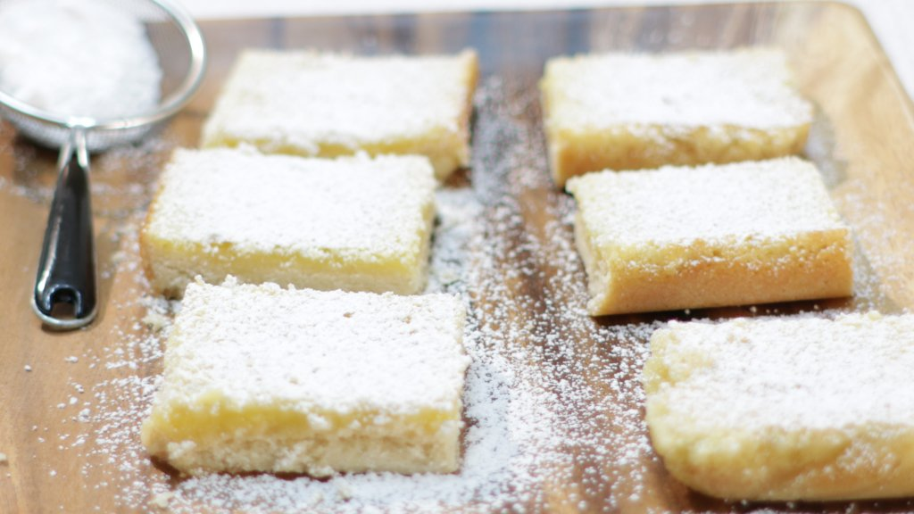 6 lemon bars covered in powdered sugar.