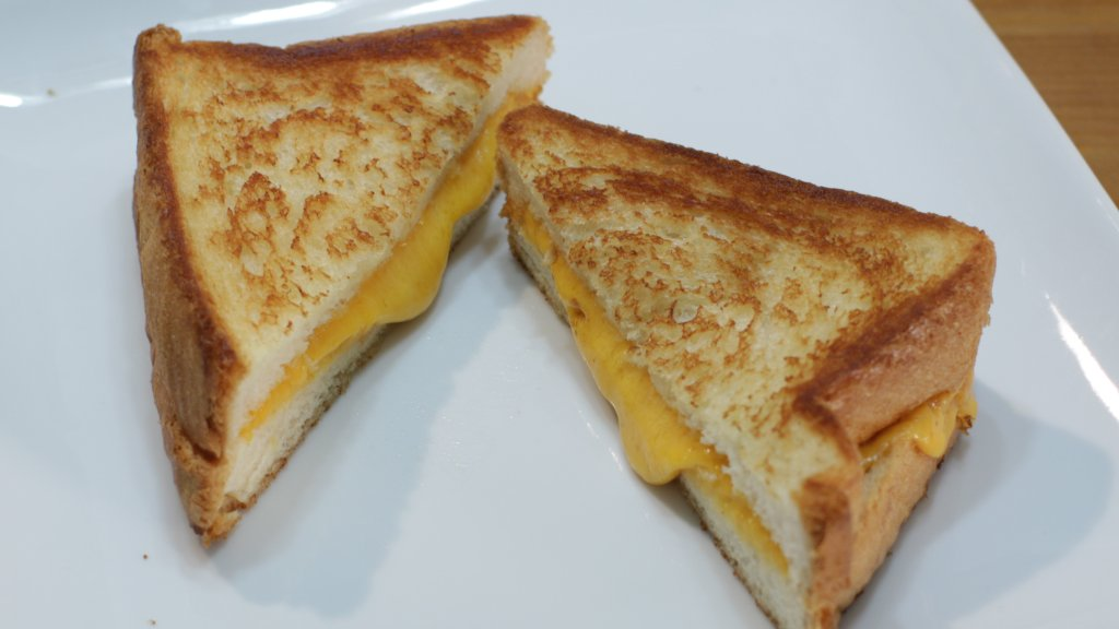 Two grilled cheese sandwich halves on a white plate.
