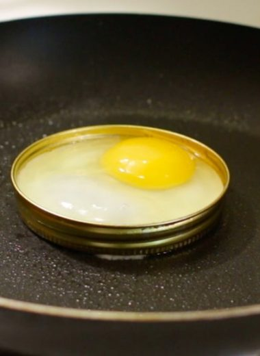An egg in a mason jar ring in a skillet.