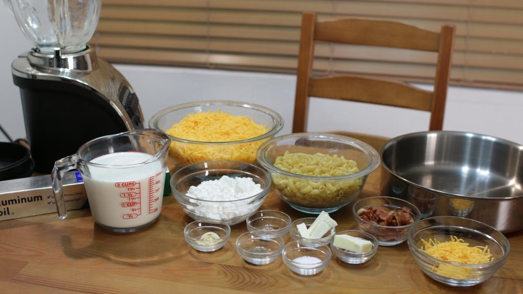 Macaroni pasta, cheese, milk, bacon, etc. in glass bowls on top of a wooden table.