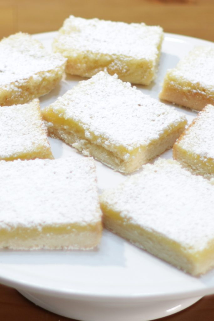 Several homemade lemon bars on a white cake pedestal.
